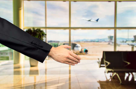 extending: business extending her hand in greeting on the airport