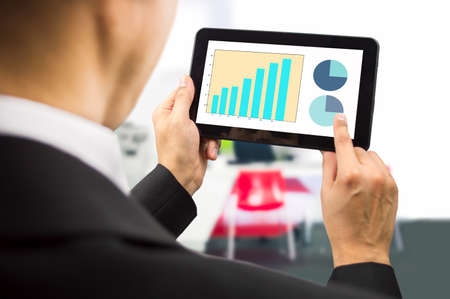 copyrighted: bussinesman looking at the stock market data on a tablet on the office.All screen content is designed by us and not copyrighted by others and created with tablet and ps Stock Photo