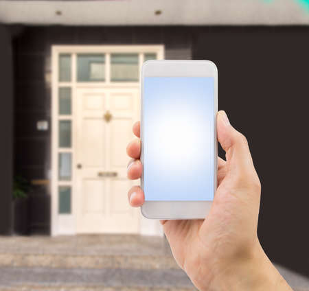 real estate sold: the hand holding the smartphone with house entry in the background like concept buy new house