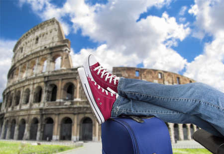 relaxed: relaxed person with feet above the suitcase on arrival in Rome Stock Photo