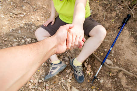 leg pain: detail of man helping with his hand to lift the woman fell in accident at the mountain Stock Photo
