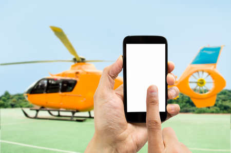 rent index: Hand holding smartphone with index finger touching the screen on the phone to rent the helicopter