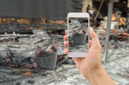 building insurance: man photographing the damages of the home affected by the fire for home insurance