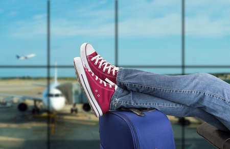 mujer con maleta: joven esperando el avión en un aeropuerto