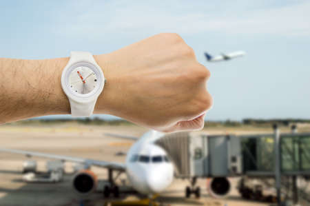 punctuality: hand with wristwatch with airport in the background as the concept of punctuality in the transport