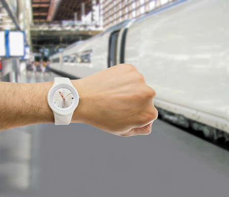punctuality: hand with wristwatch with train station in the background as the concept of punctuality in the transport Stock Photo