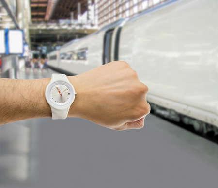 punctuality: mano con el reloj de pulsera con la estaci�n de tren en el fondo como el concepto de puntualidad en el transporte