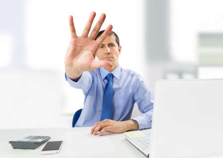 protecting your business: Businessman hand showing stop hand in concept of protecting your business interests Stock Photo