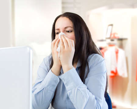 cold virus: saleswoman with a cold at the boutique