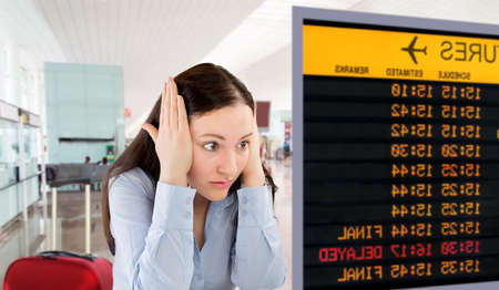 angry woman pulling with  her hands on temple because she has missed the flight Stock Photo