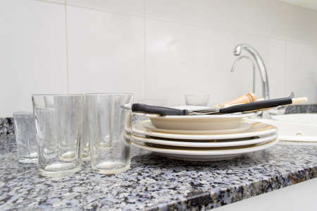 grunge silverware: stack of dirty plates and glasses on the counter of the kitchen