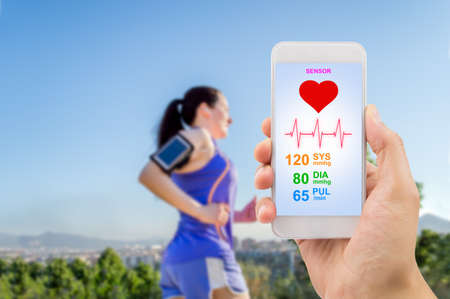 male hand holding the smartphone with mobile app health sensor to measure the athlete health. All screen content is designed by my and not copyrighted by others and created with digitizing tablet and image editor.All screen content is designed by us and n Stok Fotoğraf - 46067205