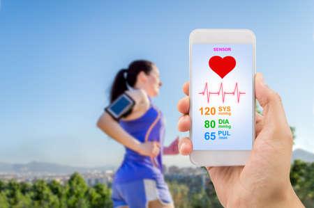 manlig hand som håller smartphone med mobila applikationen hälsa sensor för att mäta idrottaren hälsa. Allt innehåll på skärmen är designad av min och inte upphovsrättsskyddat av andra och skapade med digitalisering tablett och bild editor.All skärminnehållet är designad av oss och n Stockfoto