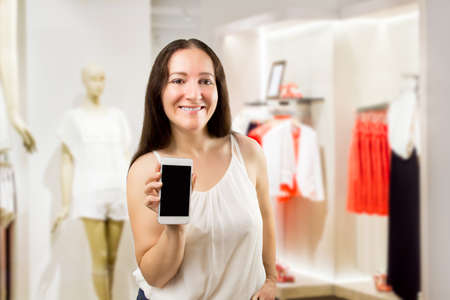 saleslady: portrait of cheerful saleslady holding and showing the smartphone at the boutique