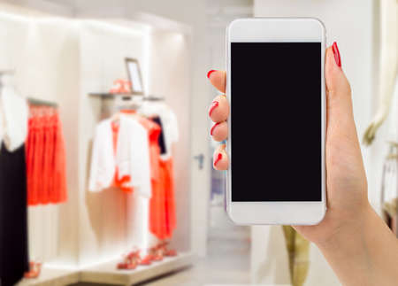 saleslady: hand woman shopping online with smartphone at the boutique Stock Photo