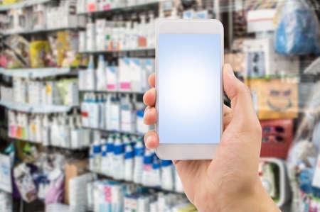 farmacia: mano que sostiene el tel�fono inteligente en la farmacia para comprar en l�nea