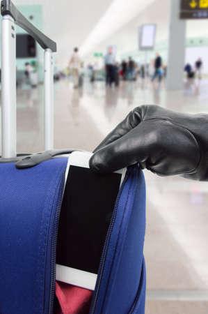 ladrón: ladr�n roba el tel�fono inteligente de la maleta en el aeropuerto