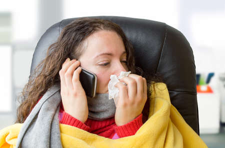 unwell: sick woman at the office calling the doctor urgently