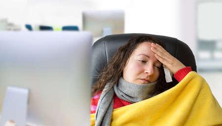 fiebre: mujer muy enferma con la bufanda y la fiebre alta en la oficina