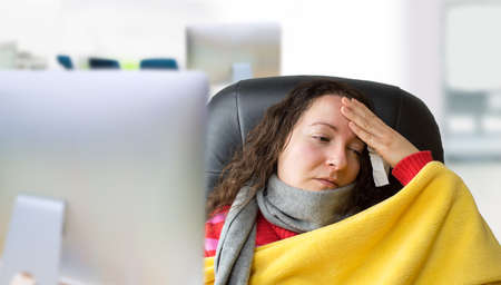sick: very sick woman with scarf and high fever at the office
