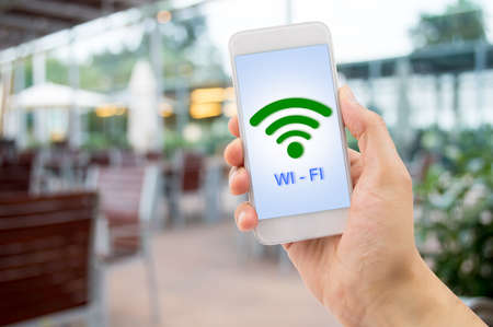 hand holding the smartphone searching the wifi signal at the terrace of bar. All screen content is designed by us and not copyrighted by others and created with digitizing tablet and image editor