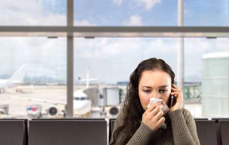 fiebre: mujer enferma llamando m�dico con urgencia en el aeropuerto Foto de archivo