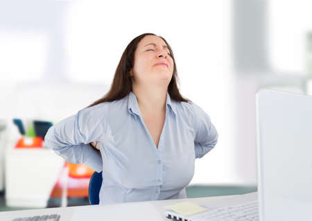business woman with a strong backache in the workplace