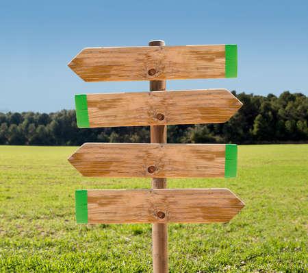 flechas direccion: señal de madera en el prado con el copyspace Foto de archivo