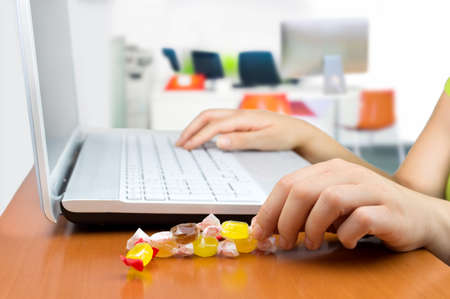 candy: woman working at the laptop eating a candy sweet Stock Photo