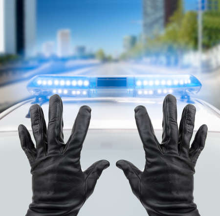 looting: robber with black gloves with hands up in front of the police car