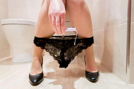 femme en sous vetements: Femme prépare à se mettre le tampon dans une toilette Banque d'images