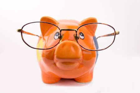 miserly: orange piggy bank is wearing glasses isolated on white background