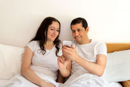 surfing the net: couple in bed surfing the net with your smart phone in the bedroom