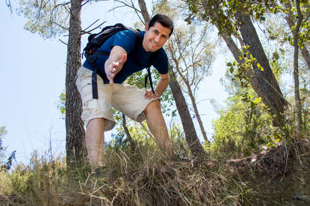 courteous: hiker man offering a hand up to get up in the forest Stock Photo