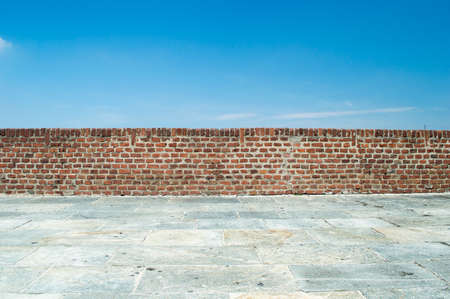 brick wall with blue sky background Imagens