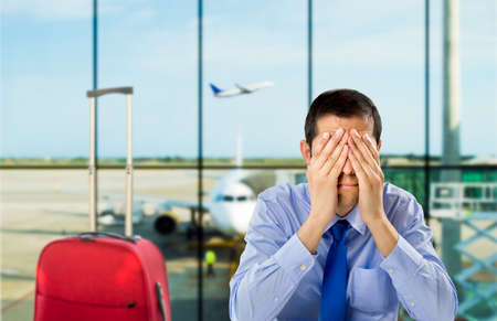 stressed people: crying businessman who delayed flight at an airport