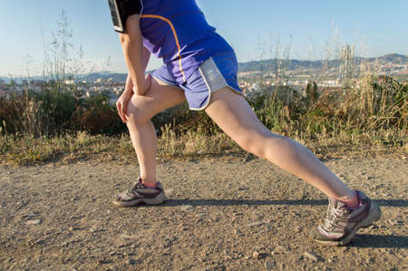 waist down: woman stretching her legs in the park