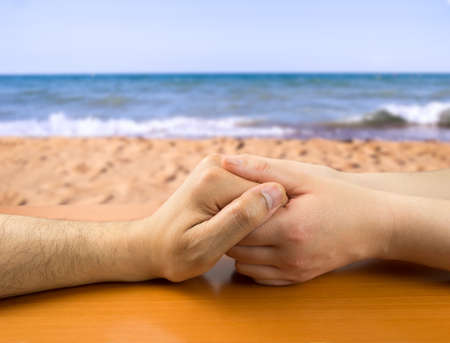 grasping: female hands grasping the concept of a man in love on the beach