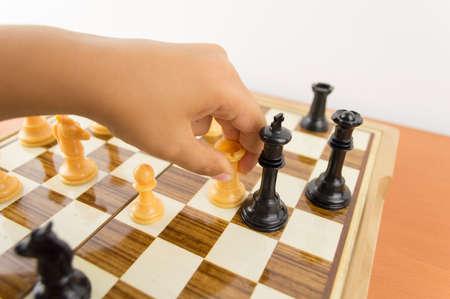 ajedrez: mano de un niño jugando al ajedrez moviendo la torre para matar al rey - haciendo que el jaque mate