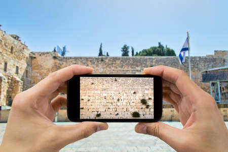 photo: tourist man taking photo with the smartphone at western wall of jerusalem israel Stock Photo