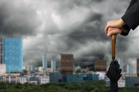 prudent: hands on an umbrella with a stormy sky in the city Stock Photo