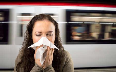 persona enferma: Mujer estornudos nariz que sopla enferma en la estación de metro Foto de archivo