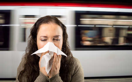 sick person: sneezing woman sick blowing nose at the subway station