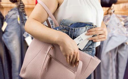 Mujer tratando de robar los pantalones de una tienda de ropa Foto de archivo - 47222886