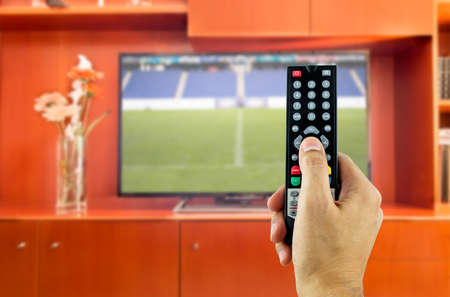 television: Hand holding television remote with sport channel Stock Photo