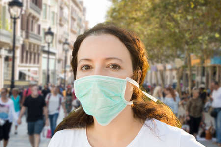 close up of an unhappy woman wearing a face mask to deal with virus or pollution on the city 스톡 콘텐츠