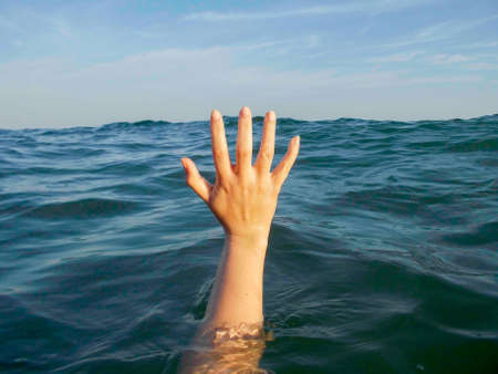 drowning: close up of hand drowning in a sea of water