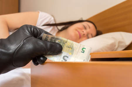 deeply: robber steals money of the nightstand while woman sleeps deeply