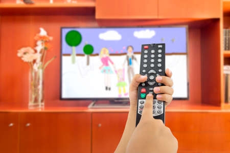 Hand of children holding television remote and watching cartoons and animated Stock Photo