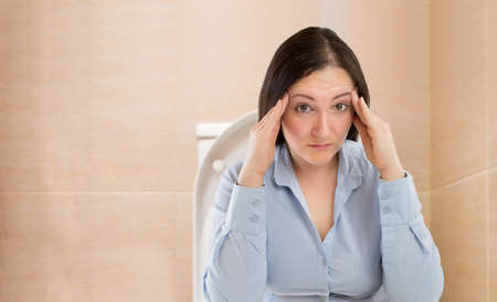 businesswoman in the toilet with problems of constipation 스톡 콘텐츠